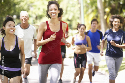 Foto  Group Of Runners Jogging Through Park