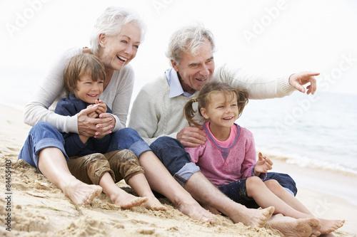 Obraz Grandparents And Grandchildren Sitting On Beach Together - fototapety do salonu