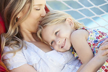 Mother And Daughter Relaxing In Garden Hammock Together