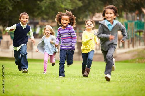 Fototapeta Group Of Young Children Running Towards Camera In Park
