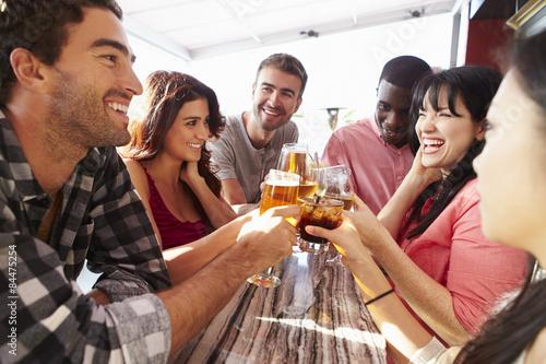 Fotografia, Obraz Group Of Friends Enjoying Drink At Outdoor Rooftop Bar