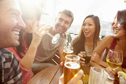 Fotobehang Bar Group Of Friends Enjoying Drink At Outdoor Rooftop Bar