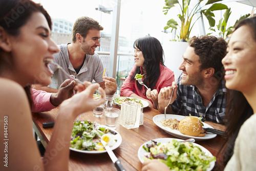 Fotobehang Restaurant Group Of Friends Enjoying Meal At Rooftop Restaurant