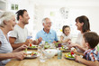 Leinwandbild Motiv Multi Generation Family Eating Meal Around Kitchen Table