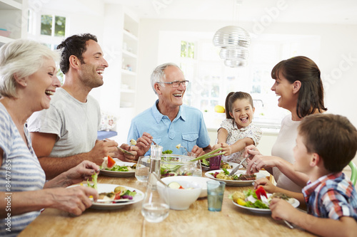 Photo  Multi Generation Family Eating Meal Around Kitchen Table