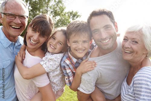 Fotografija  Multi Generation Family Giving Children Piggybacks Outdoors