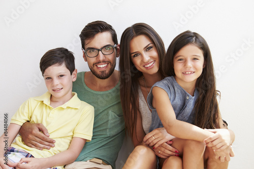 Portrait Of Family Sitting Against Wall Wallpaper Mural