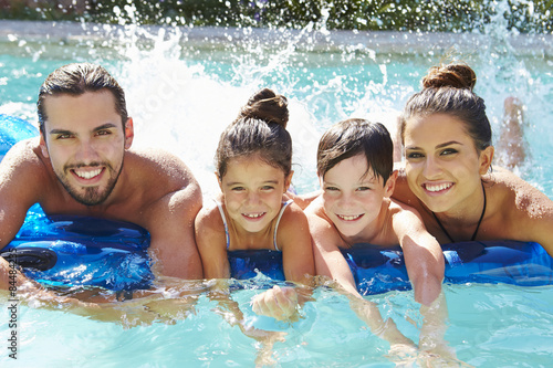 Photo  Portrait Of Family On Airbed In Swimming Pool
