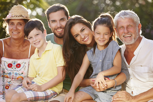 Multi Generation Family Sitting In Garden Together Wallpaper Mural