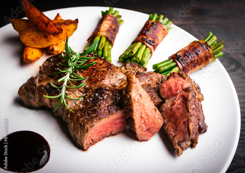 Juicy rib-eye steak with potatoe wedges and french beans Wallpaper Mural