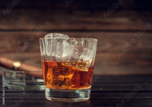 Foto op Canvas Alcohol Glass of whiskey with ice and cigar on a wooden background.