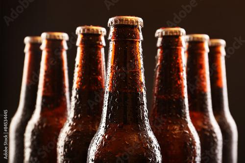 Fototapeta Glass bottles of beer on dark background