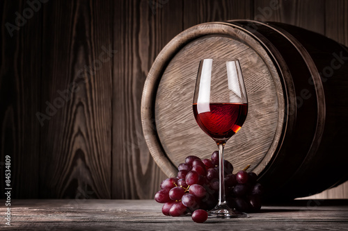 Photo  Red wine in glass and bunch of grapes