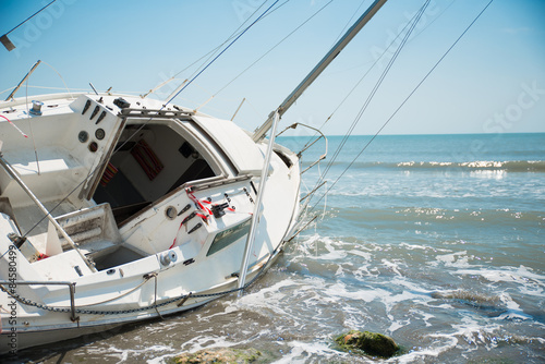 Fotobehang Schipbreuk sailboat wrecked and stranded on the beach