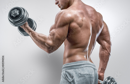 Fotografia  Power athletic man in training pumping up muscles with dumbbells