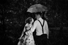 Young Romantic Couple In Love Flirting In Rain. Black And White