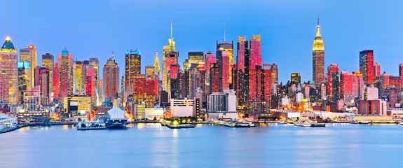 FototapetaPanoramic view of Manhattan skyline with red sunlight reflection.