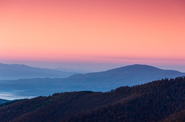 FototapetaBeautiful landscape at dawn. Layers of mountain in pink light.
