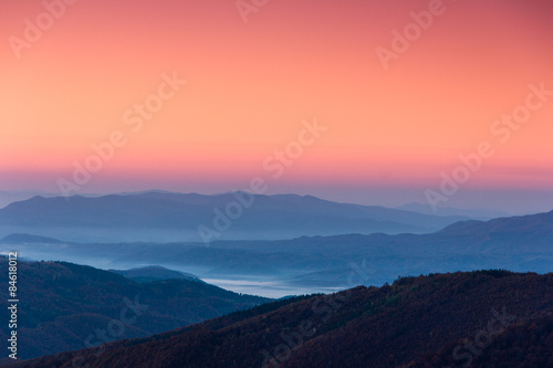 Beautiful landscape at dawn. Layers of mountain in pink light.