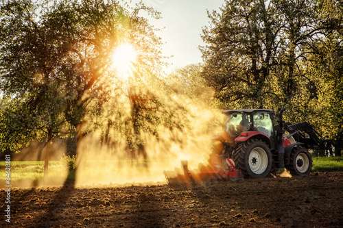 Photo  Tractor ploughing a field at sunset