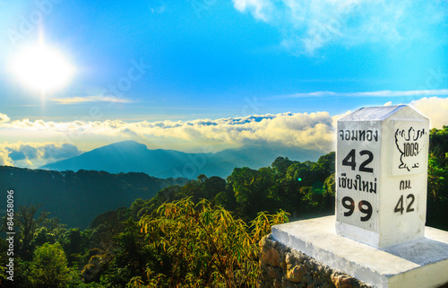 Milestone at the roadside with mountain landscape Plakat