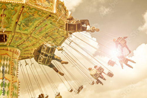 Foto op Plexiglas Amusementspark unrecognizable people on flying swing attraction, vintage process