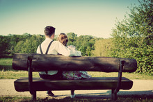 Young Couple In Love Sitting On A Bench In Park. Vintage