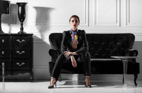young beautiful woman sitting on sofa in minimalistic inteior