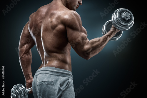 Fotografie, Obraz  Closeup portrait of a muscular man workout with barbell at gym