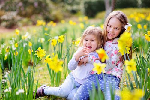 Deurstickers Narcis Cute happy little sisters cuddling and having fun in spring mead