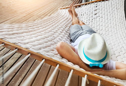 Fototapeta Man in hat in a hammock on a summer day