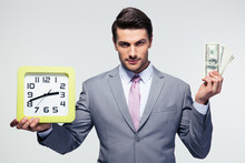 Businessman Holding Money And Clock