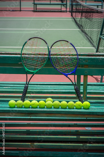 tennis racket and balls on the tennis court - 84725633