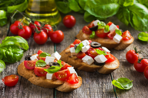 Fototapeta  bruschetta with tomato, feta cheese, olives and basil