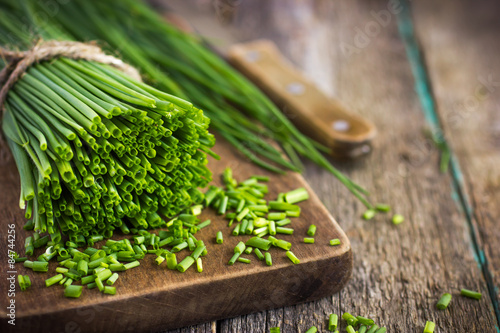 Photo  bunch of  chives on a wooden cutting board