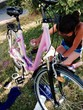 teenage girl painting. her bicycle pink