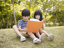 Asian Children Reading Book Outdoors