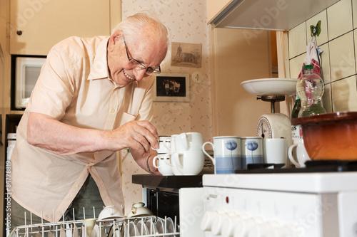 Elderly man unloading the dishwasher Wallpaper Mural
