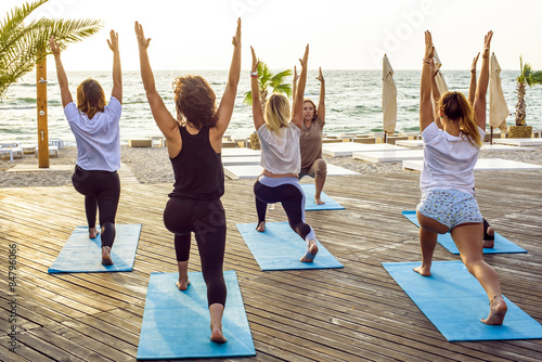 Fotografie, Tablou  group of young females practicing yoga on the seaside during the sunrisе