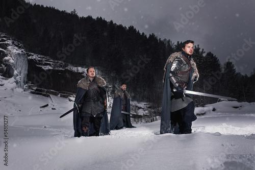 Fotografie, Tablou  Medieval knights with swords in armor walking in snow