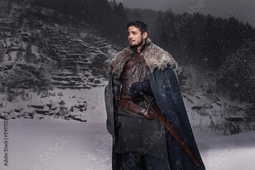 Medieval knight with sword in armor in winter rock landscape Tablou Canvas