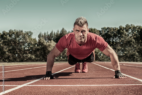 Fotografía  Handsome young shirtless Caucasian fitness man doing push-ups ou