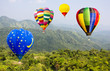 Hot air balloons on green mountain