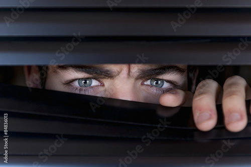 Fotografía  Joven que mira detrás de una persiana, con el ceño fruncido