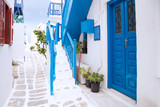 Fototapeta Fototapety na drzwi - Streetview of Mykonos town with white street, stairs and blue door, Greece