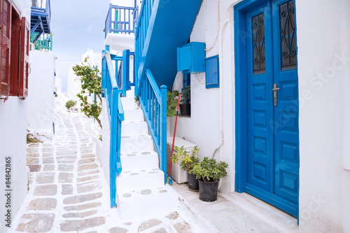 Streetview of Mykonos town with white street, stairs and blue door, Greece Wallpaper Mural