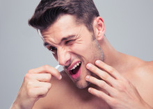 Man Removing Nose Hair With Tw...
