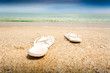 Closeup of white flip flops lying on empty sandy beach