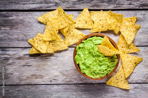 Fotografie, Obraz  homemade guacamole with corn chips top view