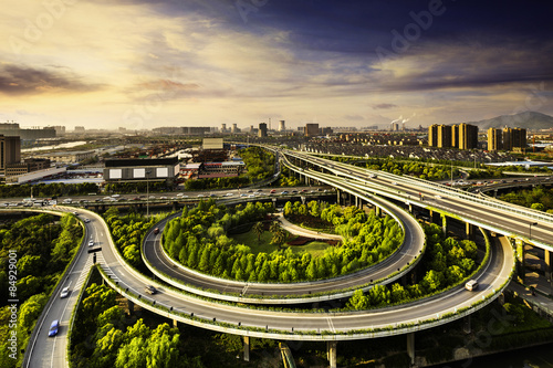 Photo  Elevated overpass with skyline of modern city during sunset.